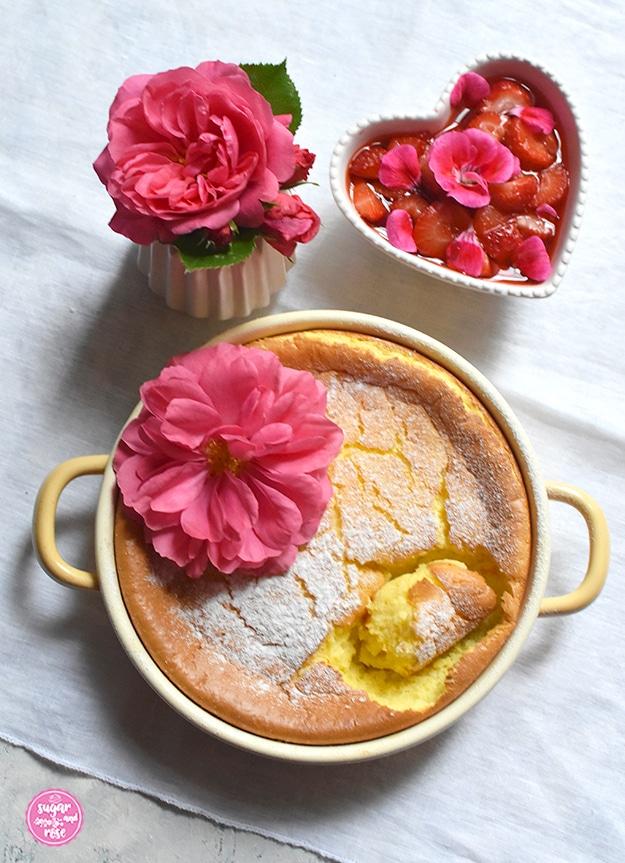 Grießauflauf in gelber Riess-Emailpfanne, dekoriert mit einer Rosenblüte, dahinter ein Erdbeer-Geranien-Kompott in herzförmiger Keramikschale, daneben eine kleine Vase mit einer pinkfarbenen Rosenblüte. Der Auflauf ist bereits probiert worden.