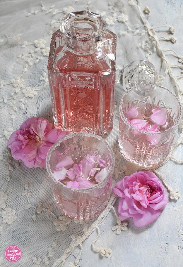 Eine geschliffene alte Karaffe mit Rosé Gin, davor zwei Gläser mit Pink Rosé-Gin und zwei Damaszenerrosenblüten