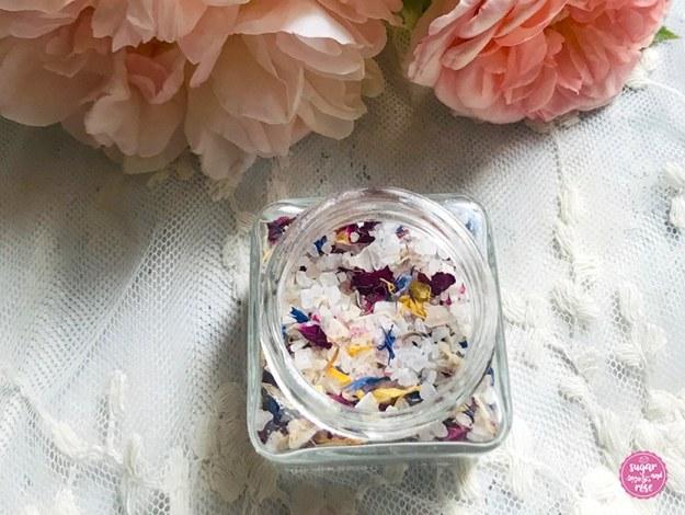 Ein kleines eckiges Glas gefüllt mit grobem Meersalz und getrockneten Blüten (Rosen, Kornblumen, Ringelblumen), dahinter einige pfirsichfarbene Rosen