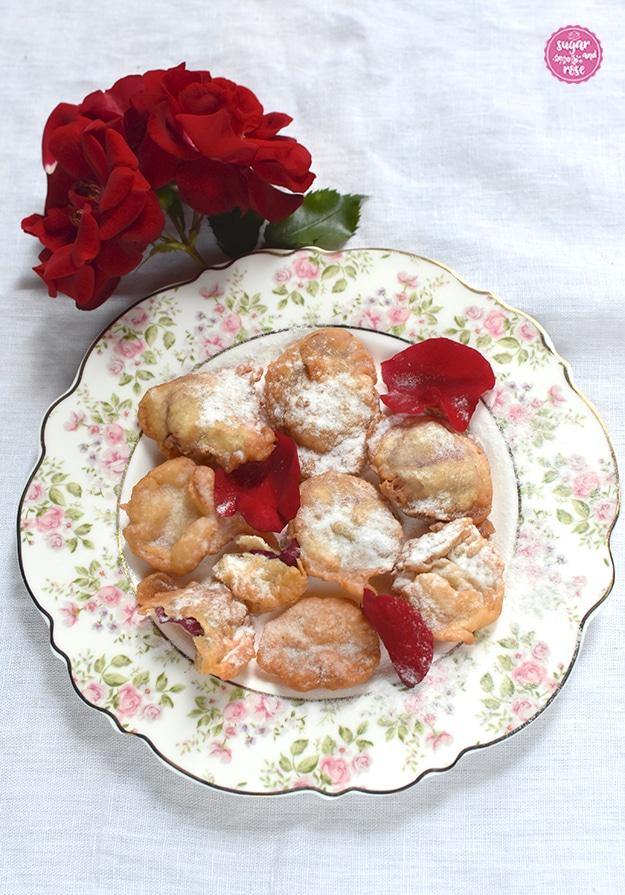 Gebackene rote Rosenblüten auf einem Dessertteller mit kleinen Röschen am Rand, dahinter Blüten einer roten Rose.