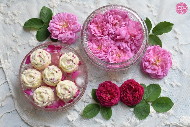 Zwei flache kleine Bleiglasschalen, eine gefüllt mit rosa Ispahan-Rosenblüten, die andere mit Eiswürfeln und Blütenblättern, darauf sieben kleine blütenförmige Rosenbutterstücke, daneben liegen noch Rosenblüten von Ispahan und der Rose de Resht