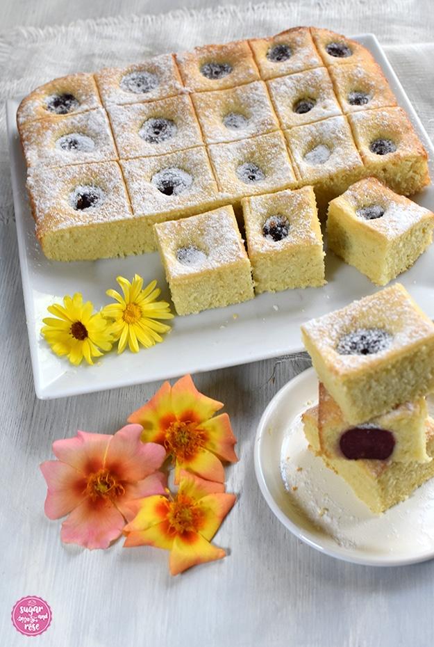 Ein quadratischer weißer Teller, darauf ein in kleine Quadrate geschnittener Kirschkuchen, davor ein kleiner weißer Teller, auf dem drei Stücke Kirschkuchen gestapelt sind, davor einige orange Rosenblüten.