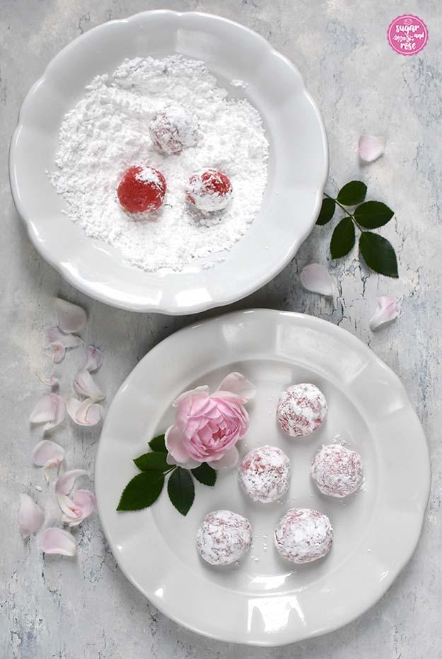Zwei weiße Keramikteller, im hinteren Staubzucker mit drei rosa Teigbällchen, davor fünf bereits in Zucker gewälzte Cookieteigkugeln.