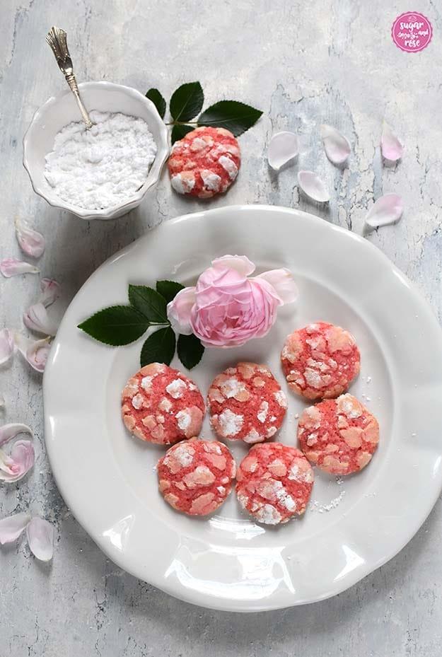 Keramikteller mit frisch gebackenen Rosen-Cookies. Nach dem Backen zeigen sich die charakteristischen Risse im Zucker und der rosa Keksteig ist zu sehen. Im Hintergrund eine Schale Staubzucker und blassrosa Rosenblütenblätter verstreut.