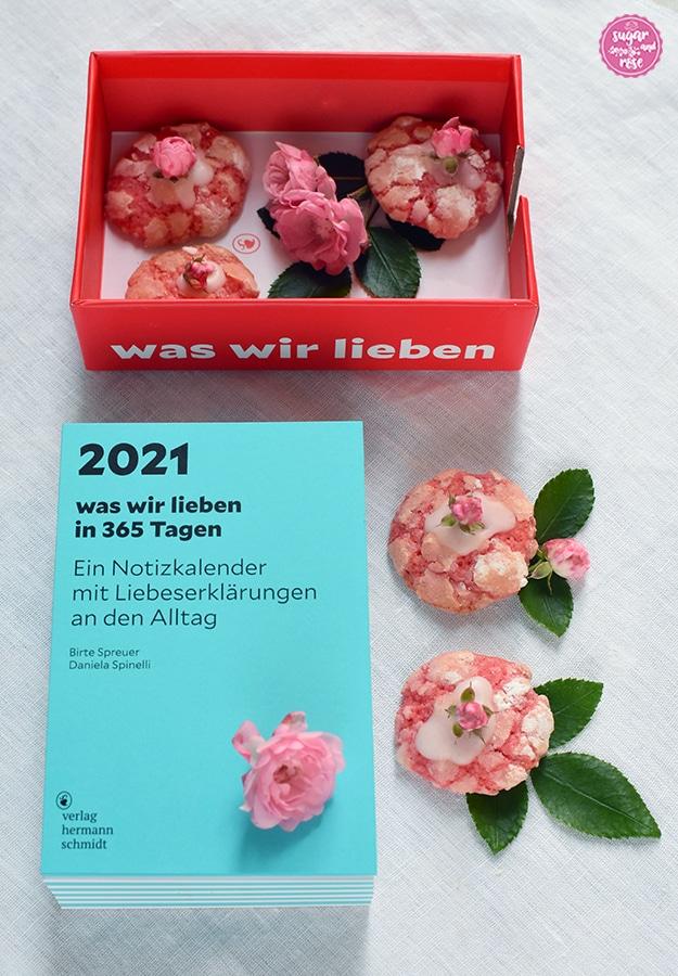 Im Vordergrund ein hellblauer Stapel von Kalenderblättern (Kalenderblock), darauf ein kleines Röschen, daneben zwei Rosen-Cookies mit kleinen Rosenblüten dekoriert; im Hintergrund die rote Kartonschachtel, mit der der Notizkalender ausgeliefert wird. In der Schachtel liegen Rosenkekse und Rosenblüten.