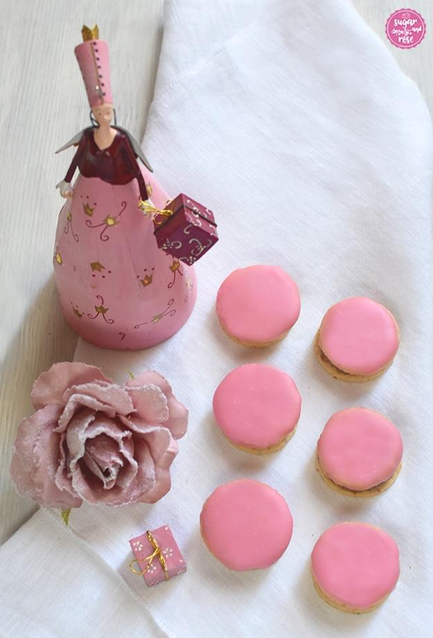 6 Punschtaler auf einer weißen Leinenserviette, daneben eine altrosa Kunstrosenblüte mit Raureif, dahinter eine rosa Blechfigur mir Engelsflügerl und einem Geschenkpaket in der Hand