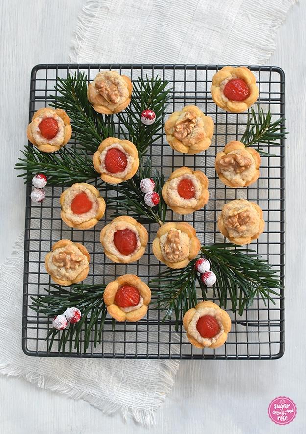 Christrosen, teilweise mit roten Belegkirschen, teilweise mit Nüssen dekoriert, auf einem Gitterrost mit Tannenzweigen als Deko
