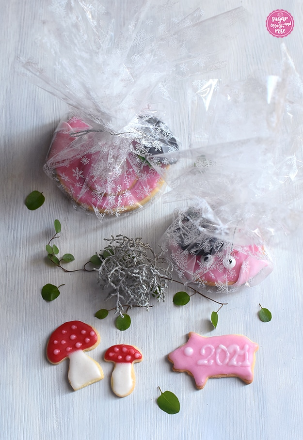 """Zwei Glücksschweinchen-Kekse verpackt in durchsichtiges Cellophan mit weißen Kristallen drauf, davor zwei Glückspilz-Kekse und ein rosa glasiertes Keks-Schweinchen mit der Aufschrift in weißer Zuckerglasur """"2021"""""""