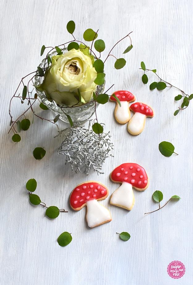 Zwei große und zwei kleine Glückspilz-Kekse mit roter und weißer Zuckerglasur, dahinter ein kleines Bleikristallväschen mit einer grün-weißen Rosenblüte und grünen Blättern