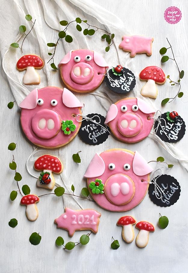 """Große und kleine Glücksschweinchen und Glückspilze mit schwarzen runden Anhängern, auf denen """"Viel Glück!"""" steht und Kleeblätter mit Marienkäferchen drauf."""