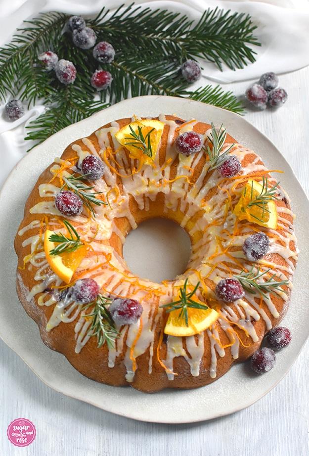 Orangen-Cranberry-Kranz mit Orangen-Icing, dekoriert mit gezuckerten Cranberrys und Orangenspalten sowie grünen Rosmarinzweigen auf einem rohweißen unregelmäßigen Keramikteller