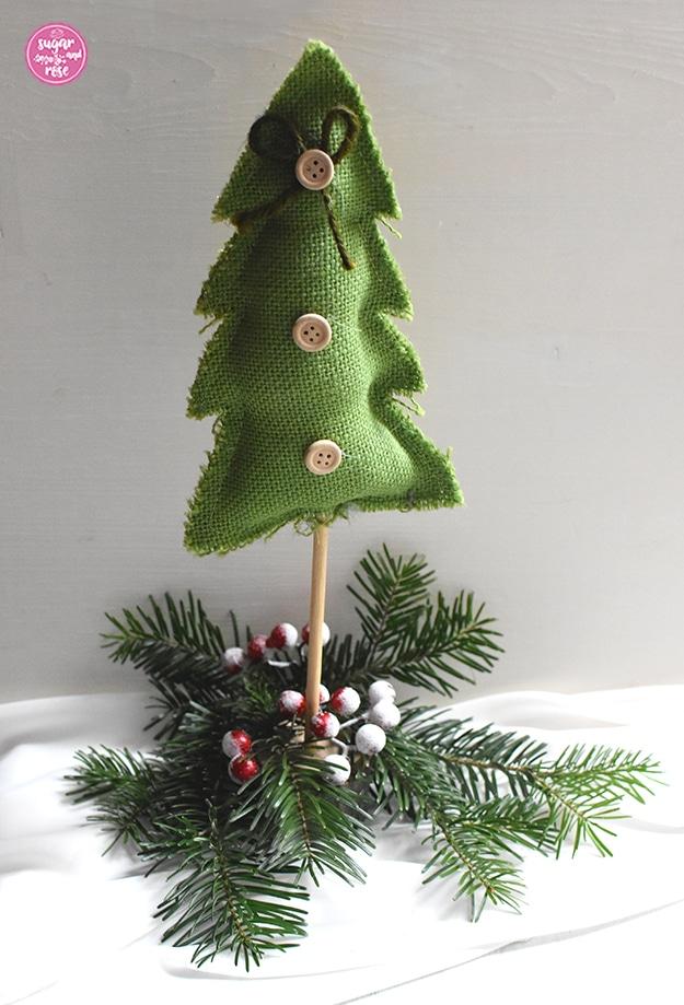 Selbstgenähter Weihnachtsbaum aus mittelgrünem Grobleinen auf einem Holzstab, dekoriert mit drei Holzknöpfen und einer grünen Masche, stehend auf Tannenzweigen mit roten kleinen Beerenfrüchten