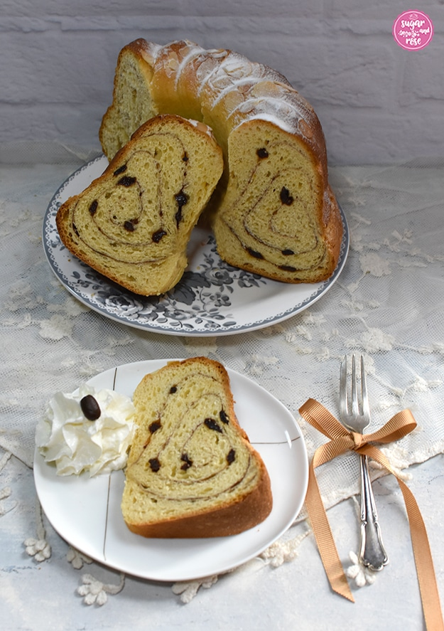 Ein halber Gugelhupf und zwei Stück davon, eines auf einem kleinen Porzellanteller liegend mit einem Tupf Schlagobers, daneben eine silberne Kuchengabel mit zimtbrauner Schleife