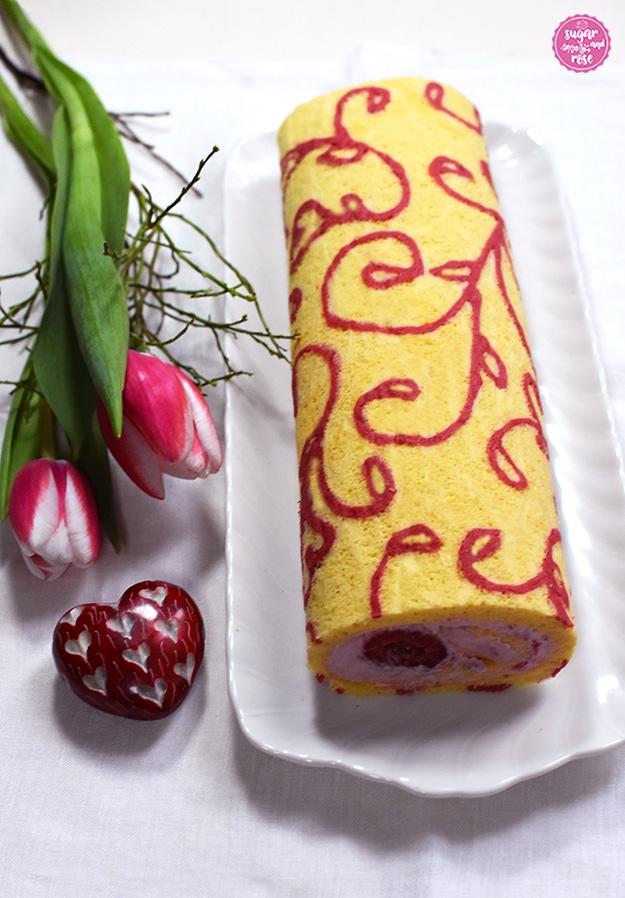 Motiv-Biskuitroulade auf weißem Porzellankuchenteller, daneben zwei rosa-weiße Tulpen und ein rotes Steinherz mit eingravierten kleinen weißen Herzen