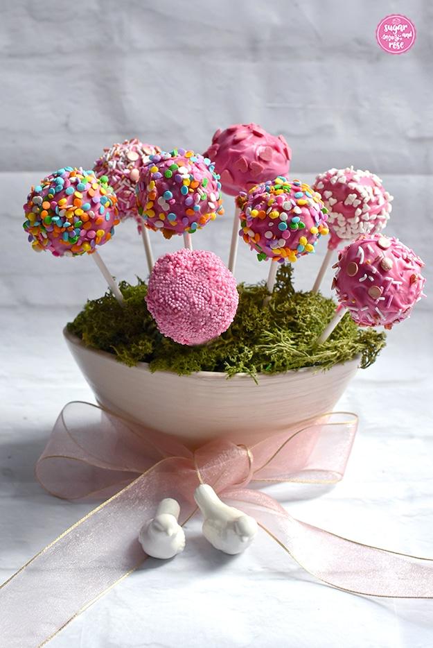Cake-Pops mit unterschiedlichem Dekor (Buntzucker, weißen Herzen, rosa-bronzefarbenen Streuseln, rosa Perlen) in einer mit grünem Moos bedeckten Keramikschale eingesteckt, davor eine durchsichtige rosa Masche und zwei kleine Porzellantäubchen