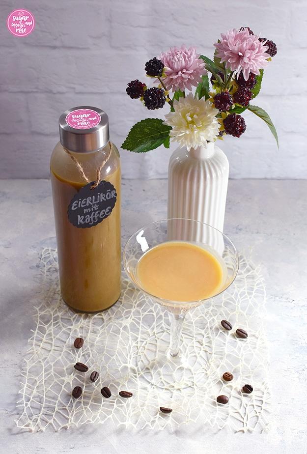 Kaffee-Eierlikör abgefüllt in Glasflasche mit beschriftetem, rundem schwarzen Etikett, am Deckel der Flasche ein rosa Kleber, davor ein Cocktailglas mit Kaffee-Eierlikör, daneben eine weiße kleine Porzeallanvase in Flaschenform mit rosa und weißen Kunstblüten sowie Brombeeren