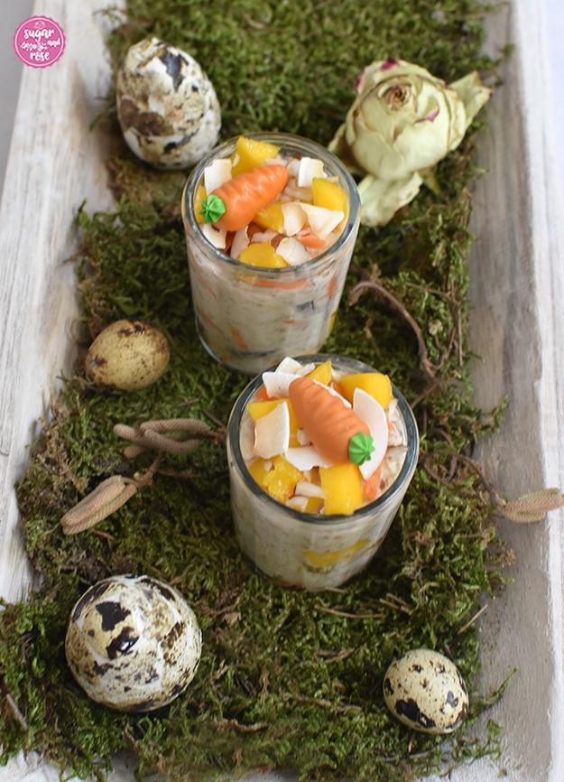 Zwei kleine Gläser mit Karotten-Overnight-Oats, dekoriert mit je einer Marzipan-Karotte. Die Gläser stehen auf einer hellen länglichen Holzschale mit Moos, dekoriert mit Wachteleiern