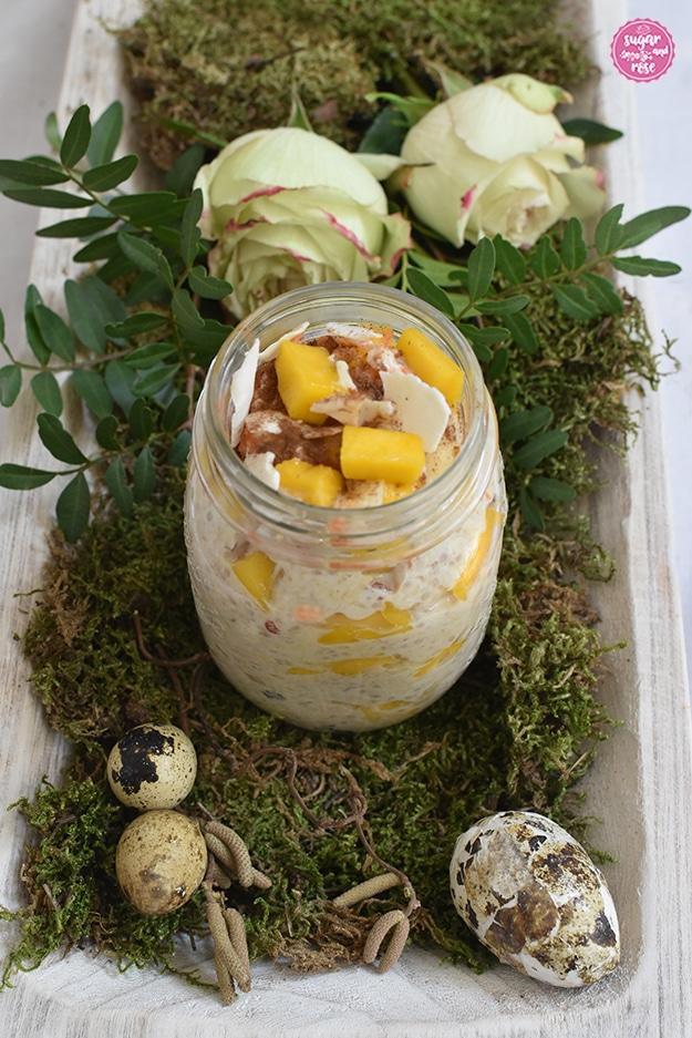 Karotten-Overnight-Oats im Schraubglas auf grünem Moos, dahinter zwei grün-weiße Rosen mit zartrosa Rand