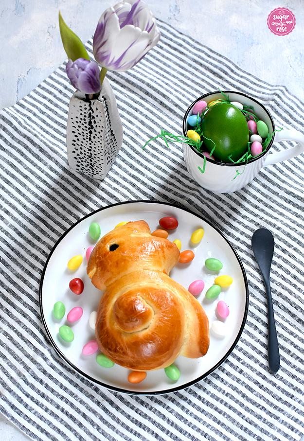 Ein Teller mit Brioche-Osterhasen, rundum bunte Zuckereier, dahinter eine Väschen mit zwei lila-weißen Tulpenblüten und ein weißes Häferl mit blauem Rand, darin ein grünes Osterei auf grünem Papierstroh, alles auf einer blau-weiß gestreiften groben Leinenserviette.