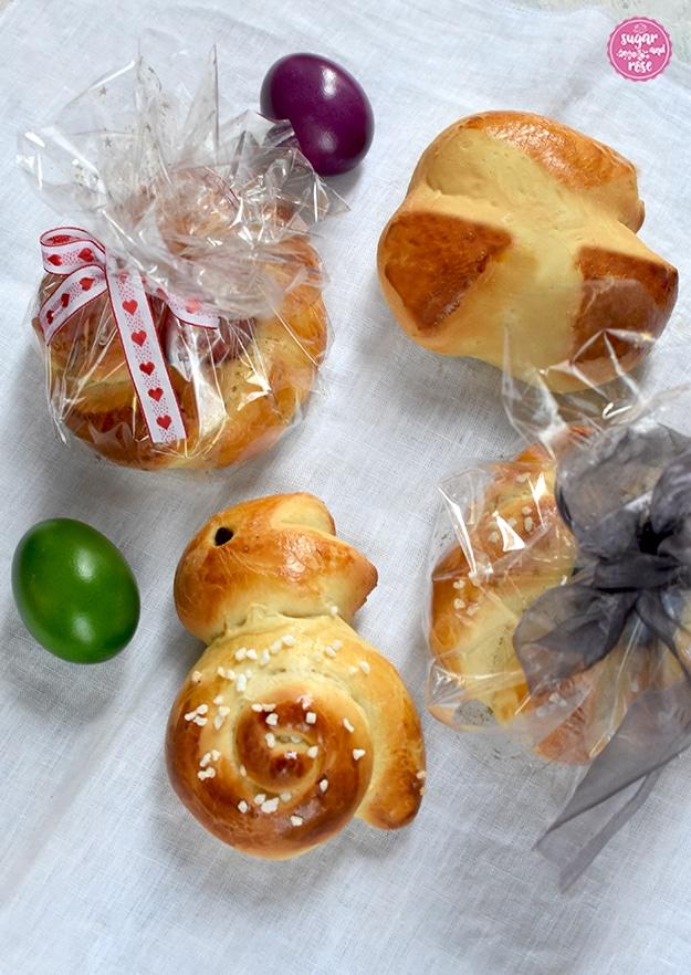 Drei kleine Osterpinzen, zwei davon in Cellophan verpackt mit Seidenmaschen, davor ein Brioche-Osterhase, daneben ein grünes und ein violettes Osterei