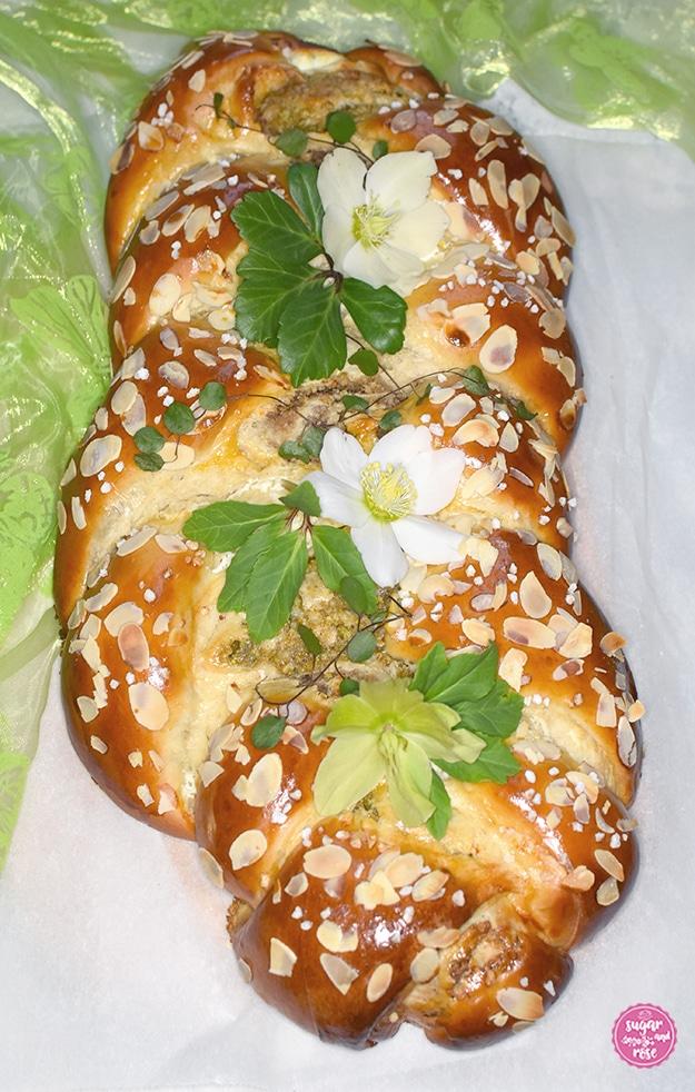 Briochestriezel (Hefezopf) mit Mandeln und Hagelzucker, dekoriert mit weißen Schneerosenblüten und grünen Blättern