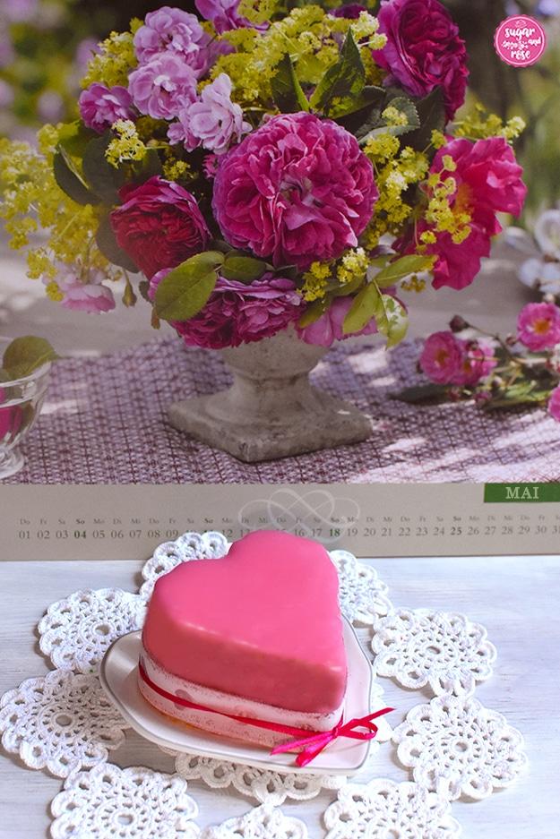 """Kalenderblatt """"Mai"""" mit rosa Rosen in einer Steinvase, davor auf einem gehäckelten weißen Deckchen ein Punschkrapfenherz auf einem herzförmigen Teller"""
