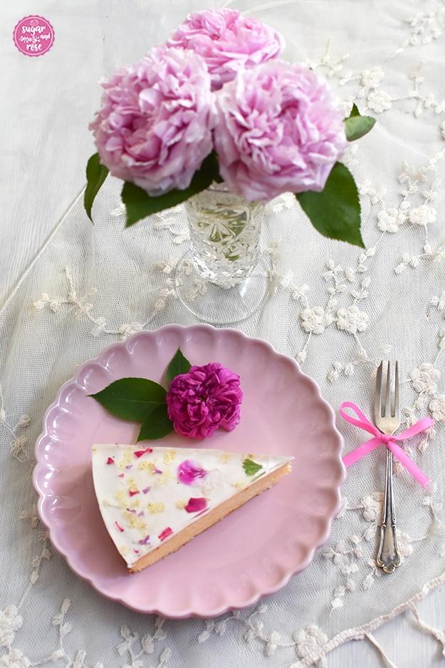 Ein Stück Topfentorte mit Blütem auf einem rosa Porezellanteller, daneben eine Vintagekuchengabel mit rosa Schleife. Im Hintergrund eine Glasvase mir rosa Rosen.