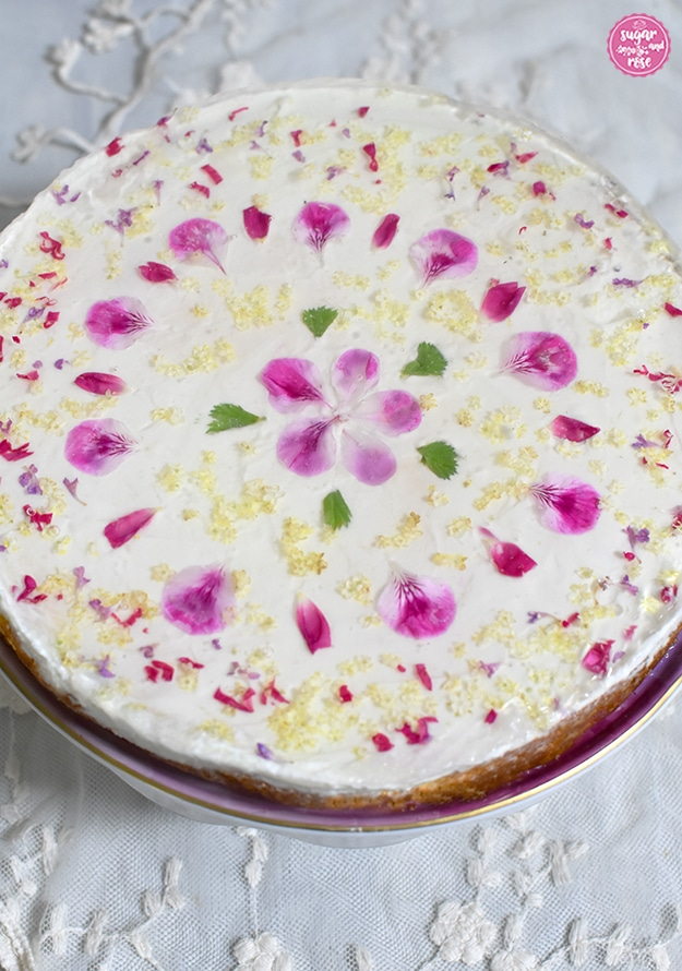 Topfentorte mit Blüten und Holundergelee in Großaufnahme, in der Mitte rosa Geranienblüten, herum grüne Geranienblätter sowie weiße Holunderblüten und kleine Stücke von Rosenblüten und Taubnesseln.