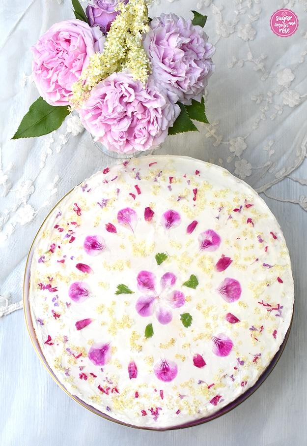 Topfentorte mit Blüten und Holundergelee von oben, in der Mitte rosa Geranienblüten, herum grüne Geranienblätter sowie weiße Holunderblüten und kleine Stücke von Rosenblüten und Taubnesseln. Hinter der Torte eine Vase mit rosa Rosen und Holunderblüten.