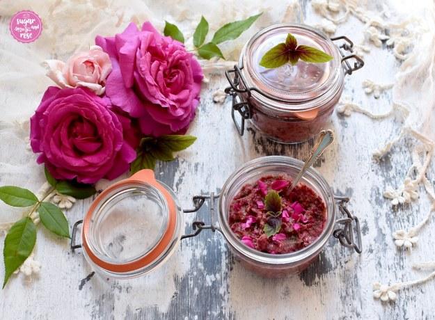Rosenpesto in Rexgläser mit Deckel gefüllt, ein Glas offen mit einem Teelöffel eingesteckt, im Hintergrund ein cremeweißes Spitzentuch und zwei pinkfarbene und eine blassrosafarbene Rose