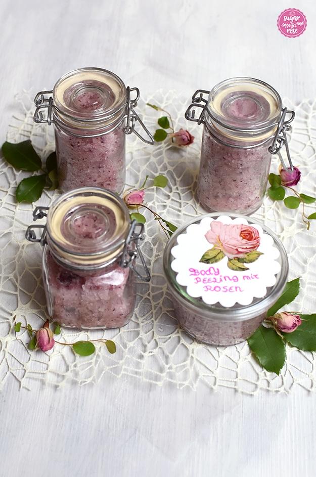 Body-Peeling mit Rosen zum Verschenken: abgefüllt in vier kleine Gläschen mit Deckelverschluss, einem weißen Kärtchen mit Rosenaufkleber und der Aufschrift Body Peeling mit Rosen