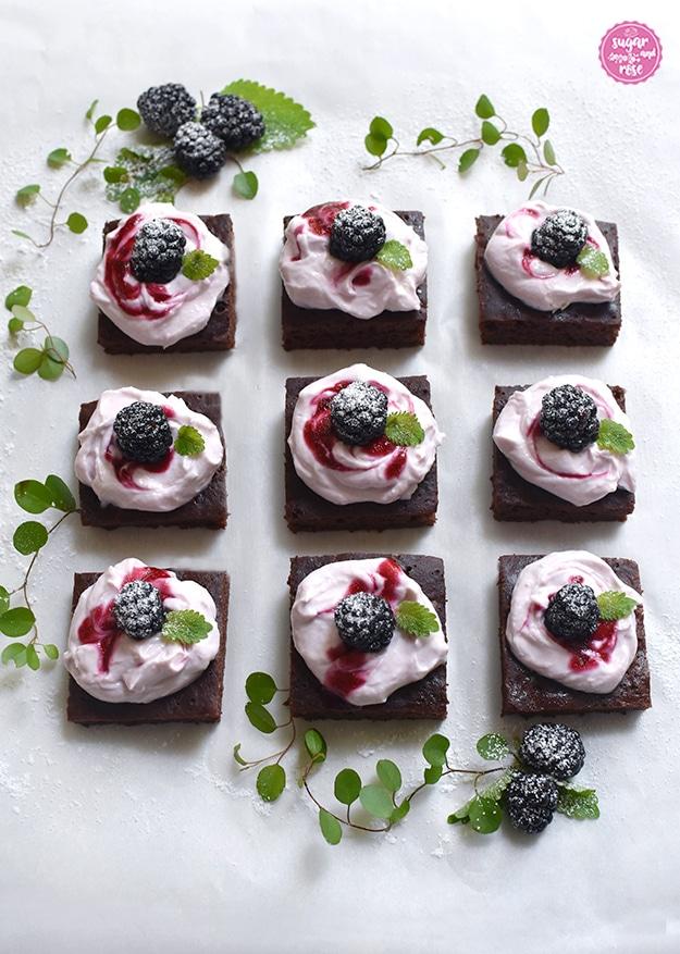 9 Stück kalorienarme Brownies mit Frischkäsetopping in Dreierreihen aufgelegt, dahinter frische Brobeeren und grüne Blätter