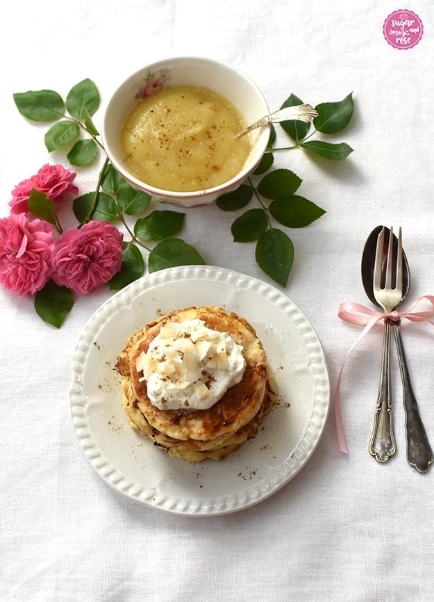 Pancakes auf weißem Dessertteller, dekoriert mit etwas Skyr und Kokoschips, daneben Dessertlöffel und Dessertgabel und eine Schale Apfelmus mit Gewürzen