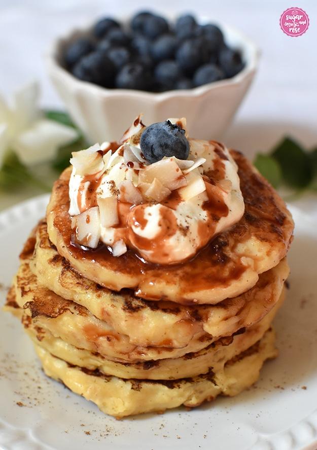 Großaufnahme von fünf Pancakes mit cremiger Deko, Kokoschips und Heidelbeeren