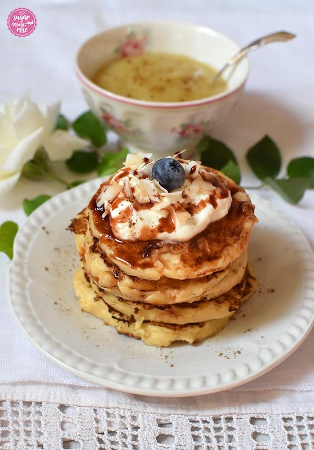 Vier kleine Pancakes übereinander gestapelt, dekoriert mit einem Klecks Topfen-Skyr und einer Heidelbeere, darüber Dattelsirup. Im Hintergrund eine Schale Apfelmus mit einem Silberlöffelchen