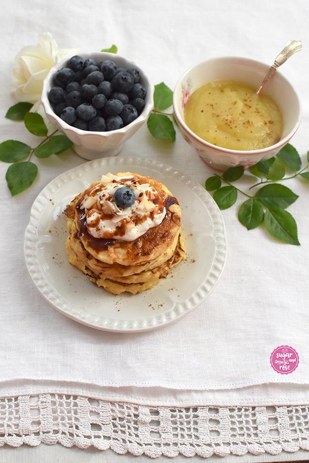 Pancakes auf weißem Porzellanteller, dahinter eine weiße Schale mit Heidelbeeren und ein Schale Apfelmus, dekoriert mit einer weißen Rose