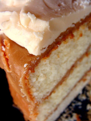 gooey caramel cake on a cake plate covered in oozing caramel and topped with fluffy caramel buttercream side shot of a slice