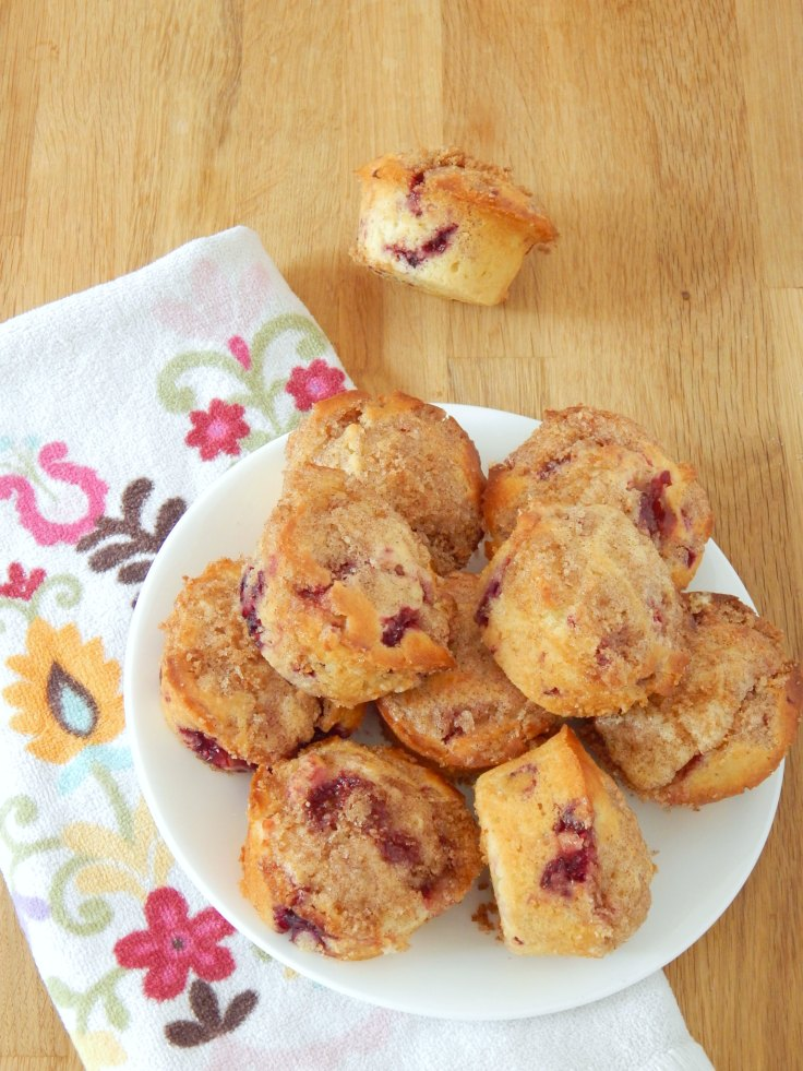 raspberry breakfast muffins fresh out of the oven on the counter with a towel