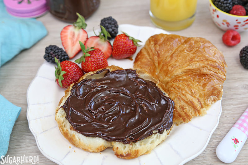 Lick-The-Knife-Clean Chocolate Spread - A croissant covered in chocolate spread with fruit on the side. | From SugarHero.com