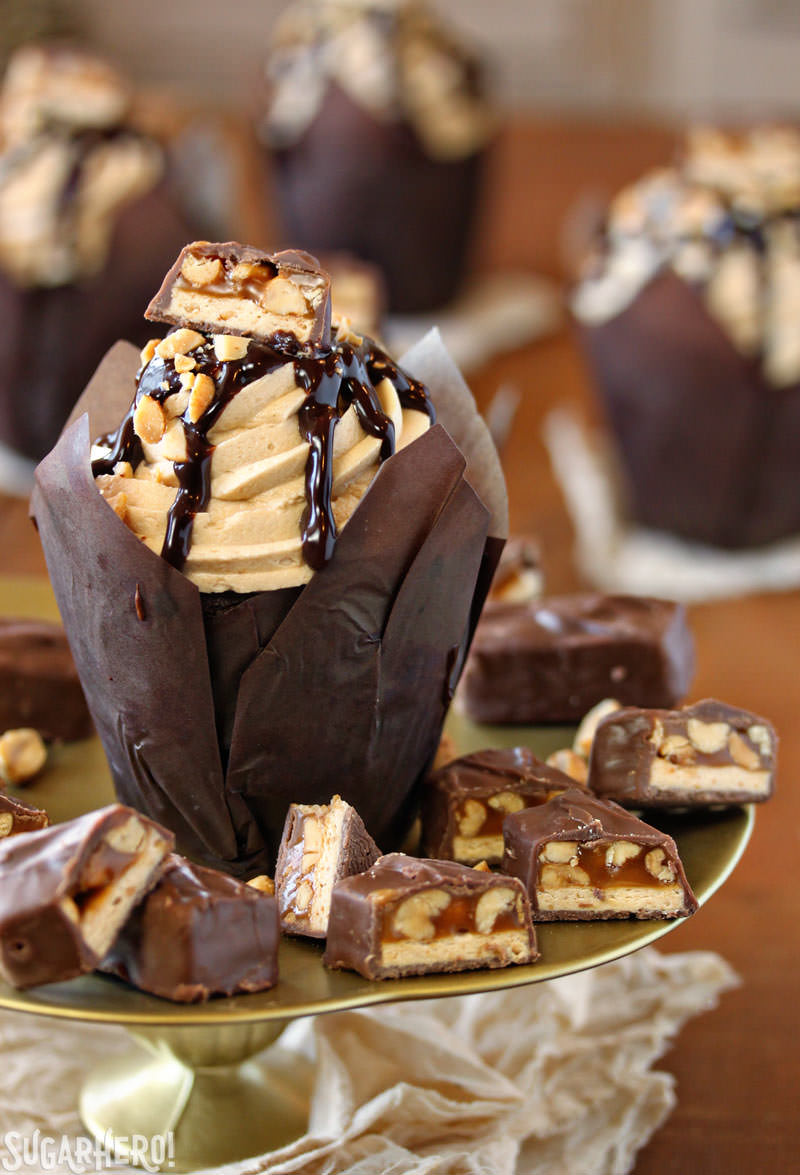 Snickers Cupcakes - A cupcake displayed on a cake stand with bits of snickers around it. | From SugarHero.com