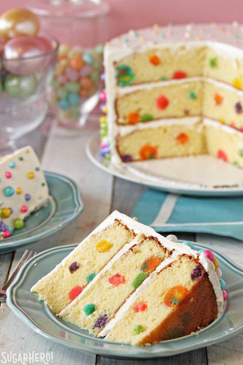 Easter Polka Dot Cake - A slice of the polka dot cake, displaying full cake in background.  | From SugarHero.com