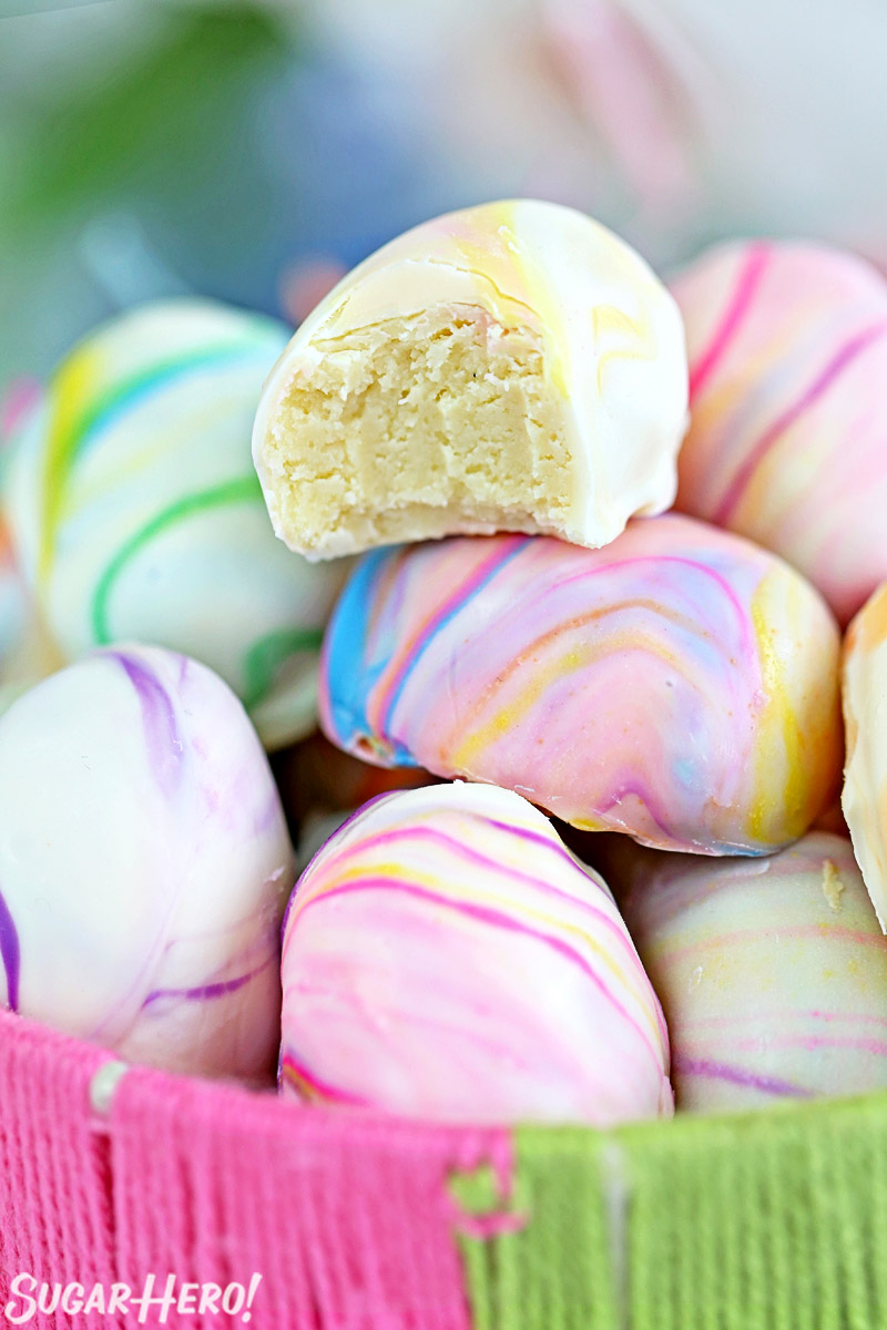 Marbled Easter Egg Truffles -A truffle with a bite taken out. | From SugarHero.com