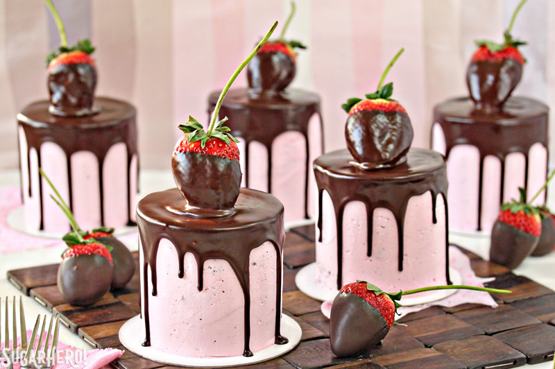 Chocolate-Covered Strawberry Cakes - Five separate cakes with strawberry's top of each and some displayed on the sides. | From SugarHero.com