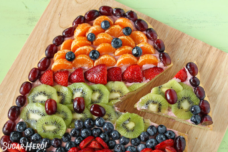 Easter Egg Fruit Pizza - Fruit pizza with a slice taken out. | From SugarHero.com