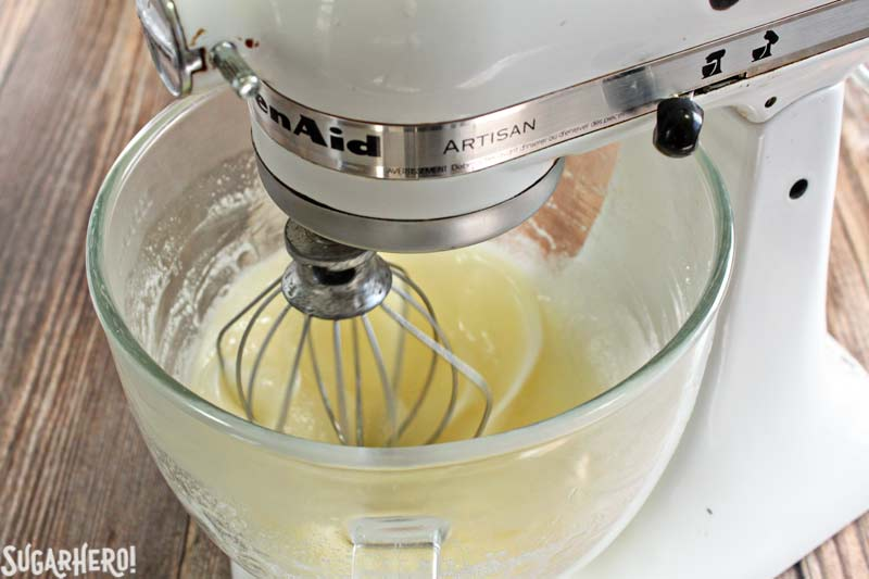 How to Make Swiss Meringue Buttercream - A close up shot of the mixture being mixed in a stand mixer. | From SugarHero.com