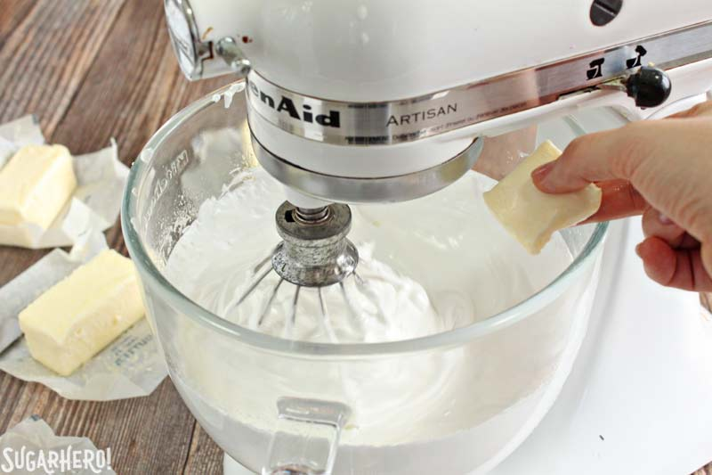 How to Make Swiss Meringue Buttercream -A shot showing the butter pieces being put into the mixture. | From SugarHero.com