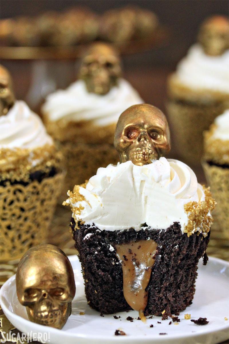 Caramel-Stuffed Chocolate Cupcakes with Caramel Skulls | From SugarHero.com