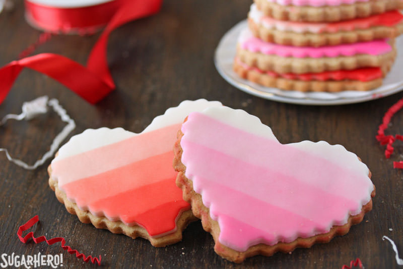 Brown Butter Heart Cookies - two sugar cookies, one red ombre and one pink ombre, with a stack of cookies behind | From SugarHero.com