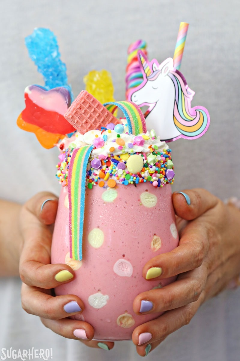 Unicorn Milkshakes - strawberry milkshakes in a polka-dot glass, topped with lots of rainbow candies. | From SugarHero.com