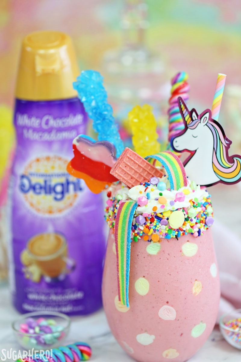 Unicorn Milkshakes - strawberry milkshakes topped with a magical assortment of rainbow candies and treats! | From SugarHero.com